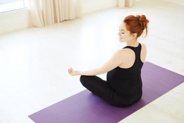 Smiling pregnant woman sitting in lotus pose