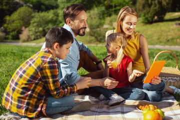 We love picnics. Delighted blond mother holding a tablet while having a picnic with her family