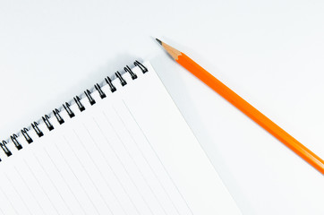 blank notebook and pencil on oblique position