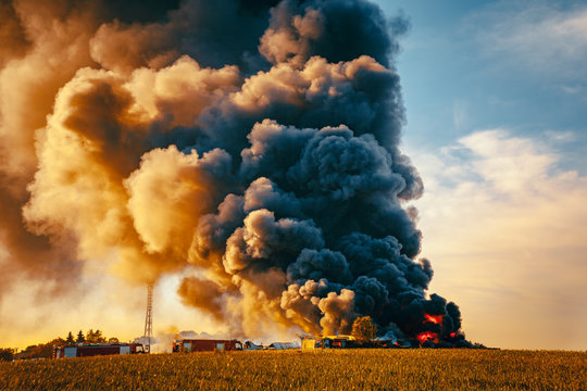 Building fire among fields and huge smoke cloud
