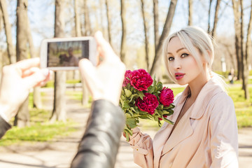 Happy young woman and male hand with smartphone. Photographer making photo on cell phone