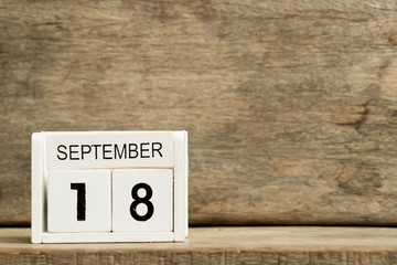 White block calendar present date 18 and month September on wood background