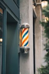 barber pole on grey wall with green wooden barber shop