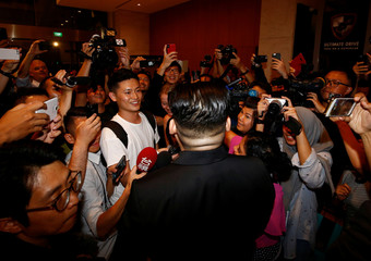 Howard, an Australian-Chinese impersonating North Korean leader Kim Jong-un speaks to people about 15 minutes after North Korea's leader Kim Jong Un left The Marina Bay Sands hotel in Singapore