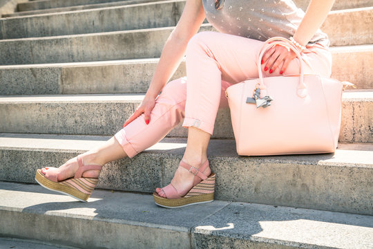 Stylish woman wearing in pink clothes on the steps.