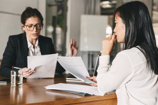 Image of nervous asian woman looking and talking to businesswoman, while sitting at table in office during job interview - business, career and recruitment concept