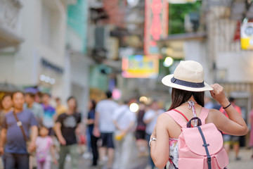 Young Woman traveling backpacker with hat, Asian traveler standing on Senado Square street, landmark and popular for tourist attractions in Macau. Travel concept
