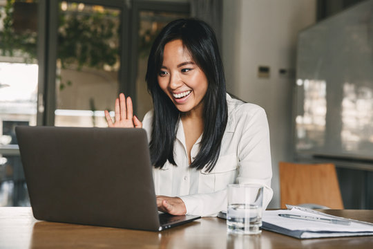 Image of happy asian woman 20s wearing white shirt smiling and waving hand at laptop, while speaking or chatting on video call in office