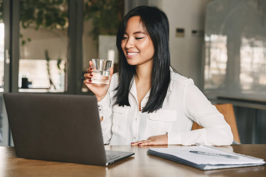 Joyful asian office woman 20s wearing white shirt smiling, while looking at screen of laptop and drinking water from glass