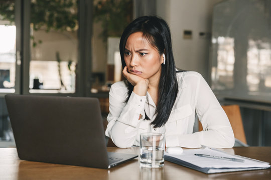 Photo of perplexed asian woman 20s wearing white shirt and bluetooth earphones frowning and looking on laptop with puzzlement, while sitting at table in office