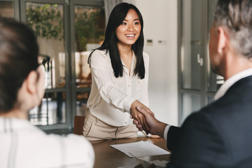Business, career and placement concept - image from back of two employers sitting in office and shaking hand of young asian woman, after successful negotiations or interview
