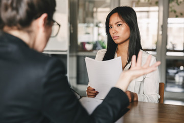 Image of serious asian woman looking and talking to businesswoman, while sitting at table in office during job interview - business, career and recruitment concept