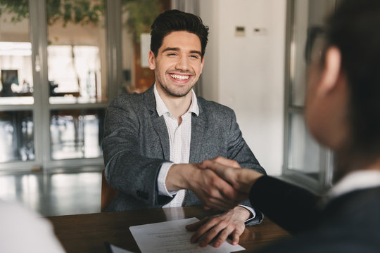 Business, career and placement concept - happy caucasian man 30s rejoicing and shaking hands with employee, when was recruited during interview in office