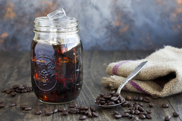 Iced Coffee in a Jar with a Spoon Full of Coffee Beans