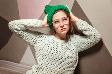 attractive woman wearing glasses and warm clothes posing near pastel wall