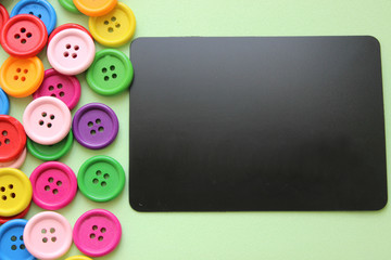 Chalk Board surrounded by colorful buttons, close-up. Concept of sewing and needlework
