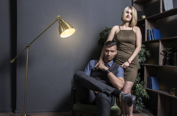 woman near with successful rich man. Young successful businessman in chair and his sexy woman in dress in luxurious apartment of wealthy house. Portrait of beautiful lovers in the interior