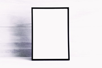 Empty blank layout photo frame on a white wooden background. Front view, copy space, mock up
