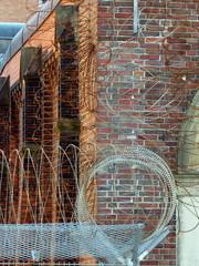 Drahtzaun und Stacheldraht vor der alten Backsteinfassade der Untersuchungshaftanstalt in der Hansestadt Hamburg