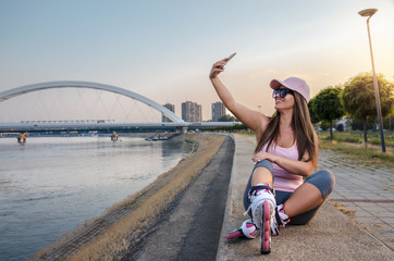 Attractive young adult woman taking selfie after roller skating by the river at sunset