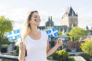 Woman celebrates the national holiday in front of Chateau Frontenac in quebec city