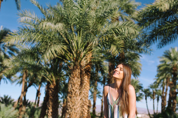 Holidays woman smiling at camera on tropical beach summer vacation with palm trees and date palms