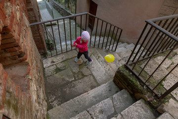 Cute little girl dressed in red playing with yellow balloon on the streets of an old town