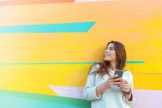 Outdoor portrait of hipster woman using a smart phone against colorful street wall