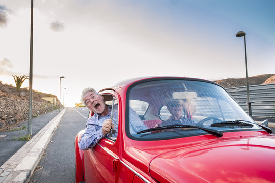 nice beautiful senior adult couple traveling together while the woman drive and the man shout for scare or for craziness. happiness and joy together forever in a perfect couple life