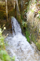 old wooden weir with water pouring out