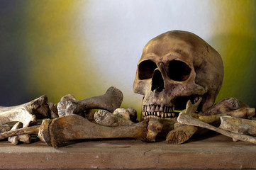 Skull and pile bones put on the wooden plank which has image moonlight on the wall background