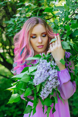 Beautiful girl with colorful dyed hair and perfect makeup and hairstyle standig next to lilac bush