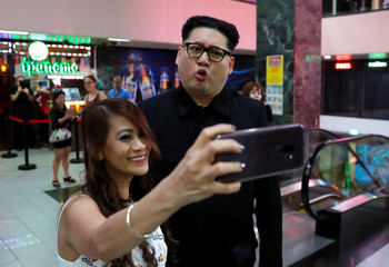 Howard, an Australian-Chinese impersonating North Korean leader Kim Jong-un, pose to a selfie in Orchard Towers in Singapore