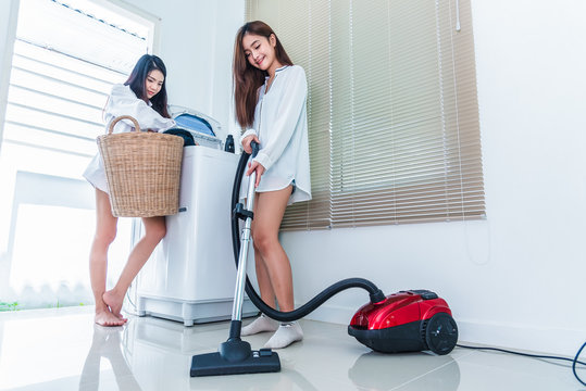 Two Asian women doing housework and chores in kitchen. Indoors activity and Lifestyles concept. Beauty lesbian theme.