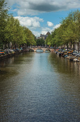 Tree-lined canal with old brick buildings, bridge, moored boats and sunny blue sky in Amsterdam. The city is famous for its huge cultural activity, graceful canals and bridges. Northern Netherlands.