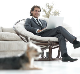 successful businessman with laptop sitting in a large comfortable armchai