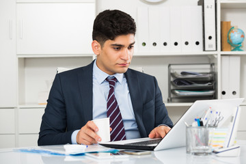 Man is working at a computer and drinking coffee