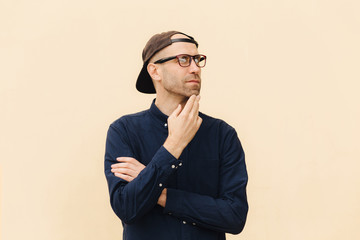 Indoor view of attractive middle aged fashionable male dressed in shirt and cap, looks pensively aside, thinks about something, poses against beige background. People, lifestyle, thoughts concept