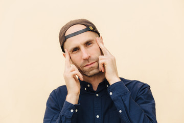 Candid shot of attractive unshaven male looks thoughtfully and concetrated at camera, keeps fore fingers on temples, wears stylish cap and shirt, isolated over light background. People and style