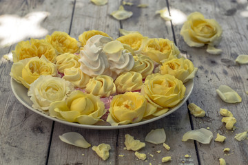 Mini Meringues of different colors and yellow roses