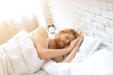 Young redhead man sleeps under white blanket.