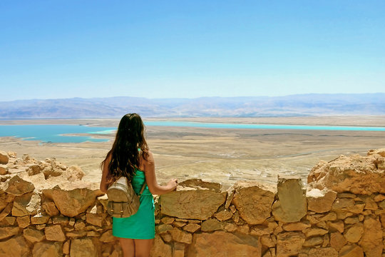 A young girl looks at the Dead Sea. Ruins of Herods Castle in  Masada Fortress in  Israel
