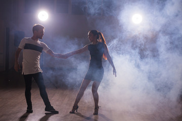 Skillful dancers performing in the dark room under the concert light and smoke. Sensual couple...