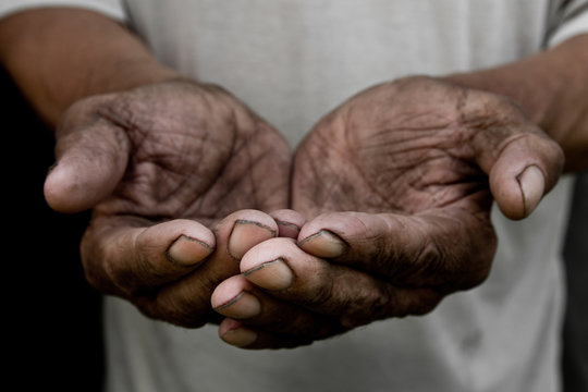 The poor old man's hands beg you for help. The concept of hunger or poverty. Selective focus. Poverty in retirement. Alms