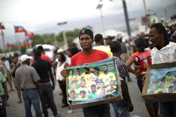 Two men sell posters of the Brazilian national soccer team as workers gather to protest in Port-au-Prince