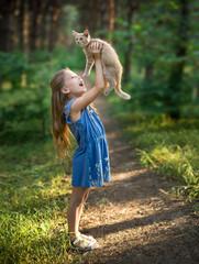 Little pretty girl is holding ginger kitten. Pets concept. Outdoor scene