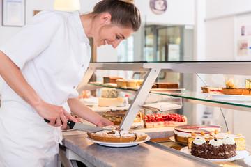 Bäcker oder Konditor Frau packt Kuchen in die Vitrine