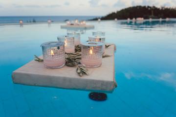 Kerzen schwimmen im Pool auf Party im Strandhaus