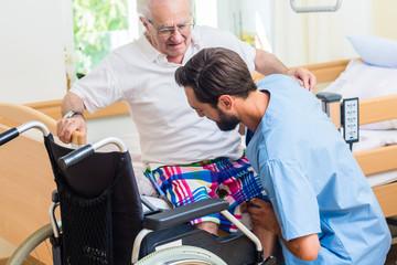 Altenpfleger hilft älterem Mann aus Rollstuhl ins Bett