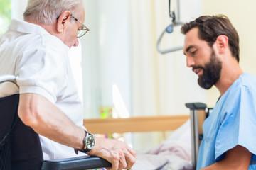 Altenpfleger hilft Senior aus Rollstuhl ins Bett